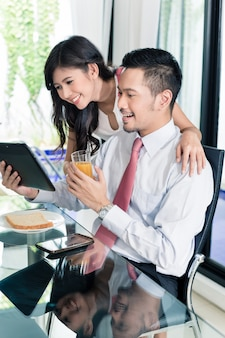 Couple having breakfast before man goes to office