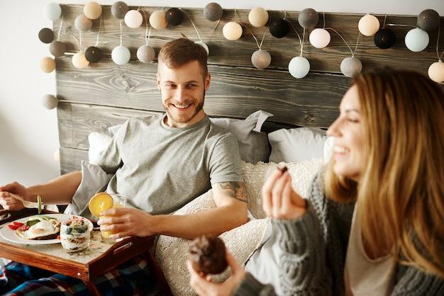 ベッドで朝食をとっているカップル