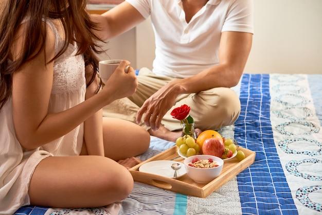 Пара завтракает в спальне