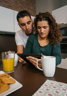 Пара завтракает на кухне и смотрит на планшет