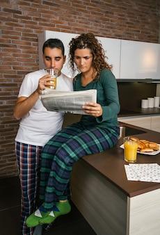 キッチンで朝食をとり、新聞を読んでいるカップル