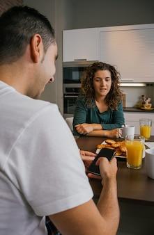 Пара завтракает на кухне с мужем, глядя на мобильный телефон