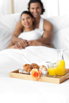 ベッドで朝食をしているカップル
