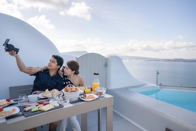 朝食をとるカップル、観光客は屋外のテラスホテルで自分撮りをします。贅沢で美味しい料理。サントリーニ島、ギリシャ。