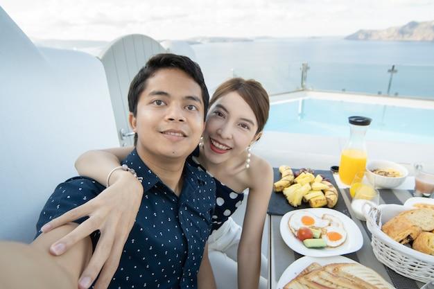 朝食の観光客が屋外のテラスホテルで自分撮りをするカップル