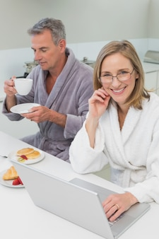 Couple having breakfast while using laptop in kitchen