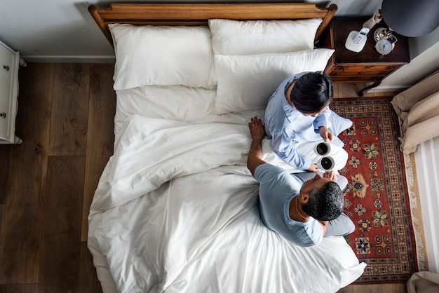 Couple having coffee on bed together