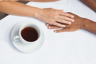 Couple having coffee together holding hands
