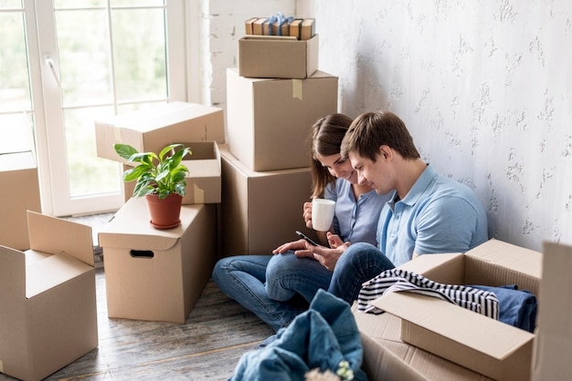 Couple having coffee while packing to move house
