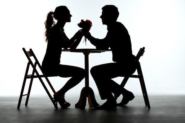 Пара обедает с бокалом вина на столе. силуэты на белом фоне