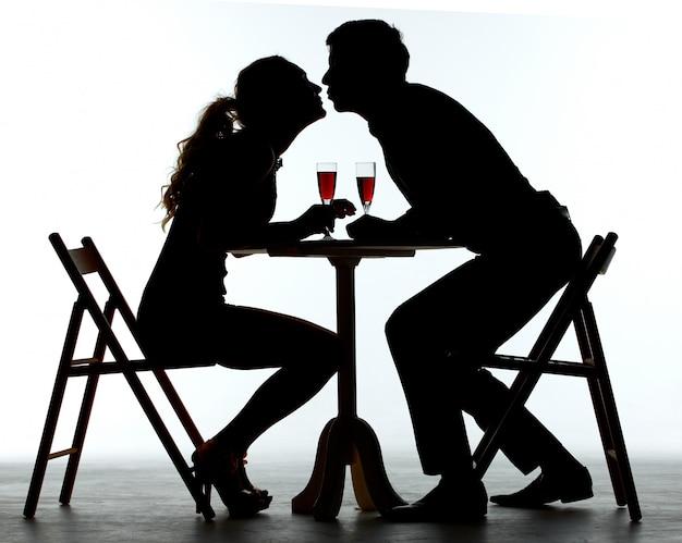 テーブルの上のワイングラスとディナーを持っているカップル