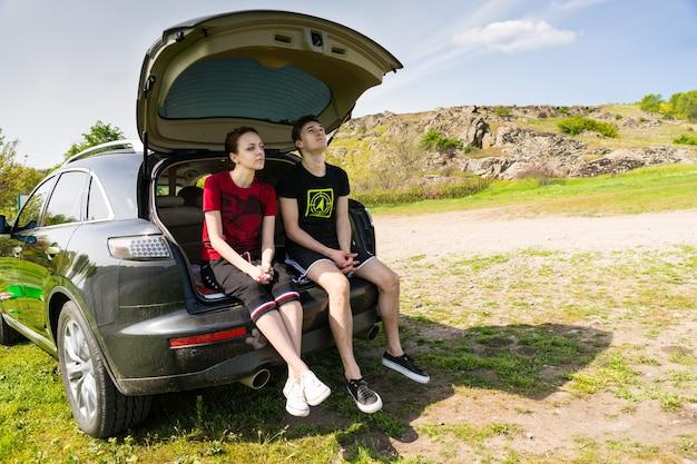 한적한 비포장 도로 옆에 주차된 차량의 뒷문에 의견이 다르고 멀게 보이는 커플