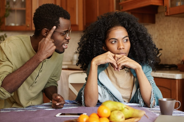 Couple having dispute. annoyed beautiful dark-skinned female sitting at kitchen table, ignoring screams and insults from her mad furious husband who is shouting at her, holding finger at his temple