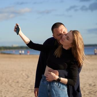 カップルが楽しんで、夏や秋の砂浜のビーチで携帯電話でselfie写真を撮る。