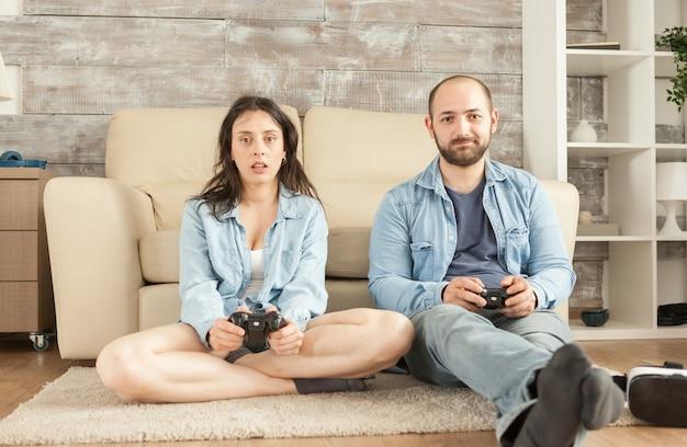 ワイヤレスコントローラーでビデオゲームを遊んで家で楽しんでいるカップル