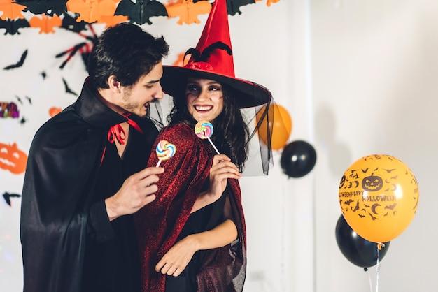 Пара весело проводит время, держа тыквы и одетые в карнавальные костюмы хэллоуина