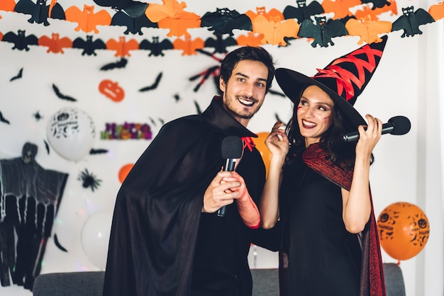 Couple having fun holding pumpkins and wearing dressed carnival halloween costumes and makeup posing with bats and balloons