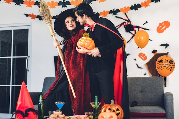 Couple having fun holding pumpkins and wearing dressed carnival halloween costumes