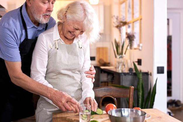 健康的な食事をしながらキッチンで楽しんでいるカップル、自宅で食事を作っている、バイオフレッシュな野菜でランチを準備している、野菜を彫ったり切ったり、男性はエプロンを着て妻を助けます