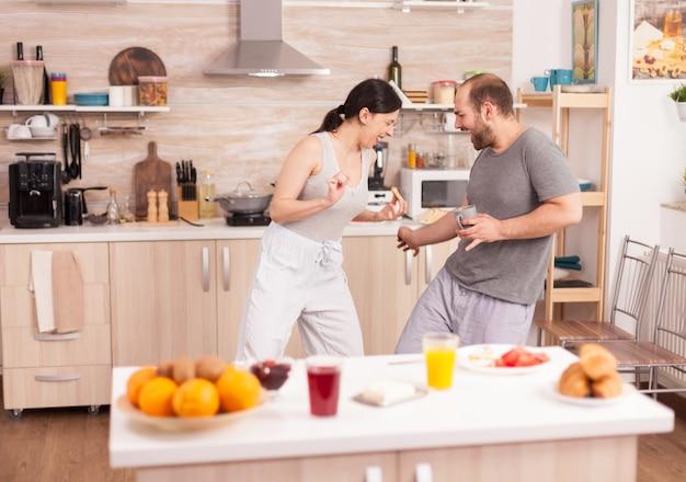 朝食時にパジャマを着て大きなスプーンでキッチンの柵で楽しんでいるカップル。陽気なのんきな楽しい面白い恋人たち、木のスプーンとの戦い、ゲームの戦いの剣術、幸せなライフスタイルの戦い