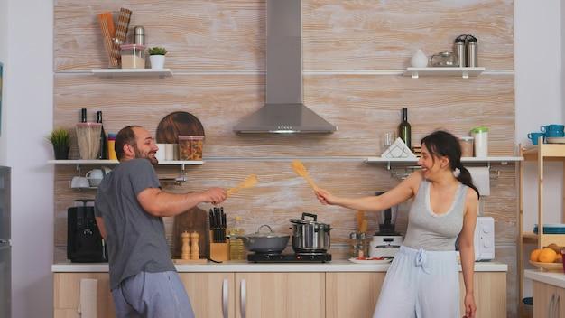 朝食時にパジャマを着て大きなスプーンでフェンシングをしているキッチンで楽しんでいるカップル。陽気なのんきな楽しい面白い恋人、木のスプーンとの戦い、格闘ゲームの戦いの剣術、幸せなライフスタイル
