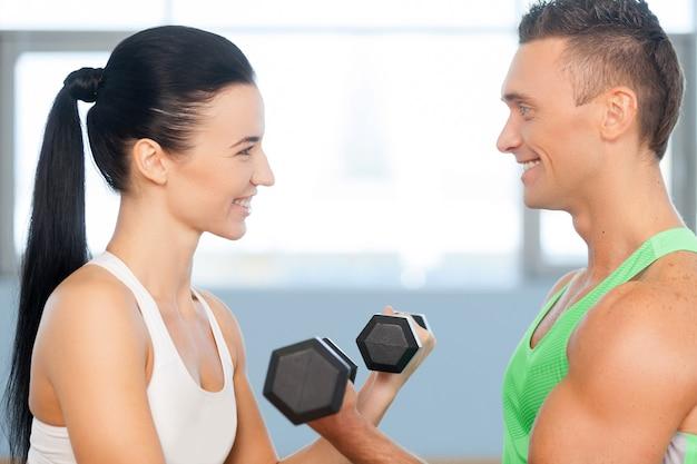 ウェイトリフティングを楽しんでいるカップル。ダンベルを持つ運動の男性と女性