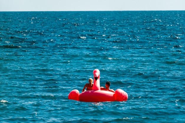 Couple having fun on pink flamingos at blue sea. sunset holiday travel vacation