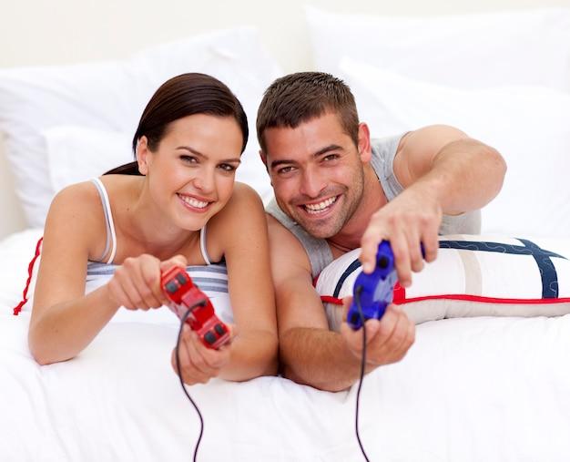 ベッドでビデオゲームをするのが楽しいカップル