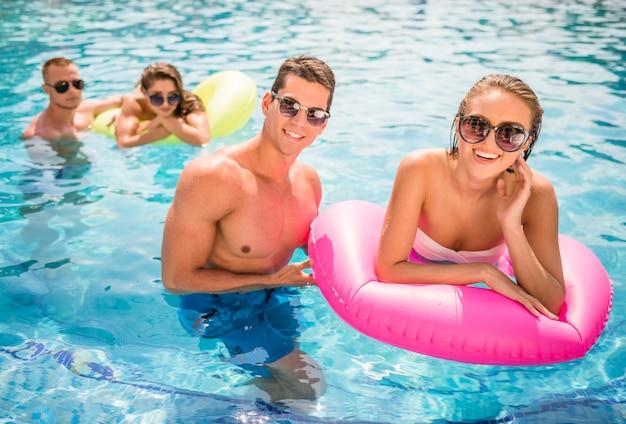 Couple having fun in swimming pool, smiling.