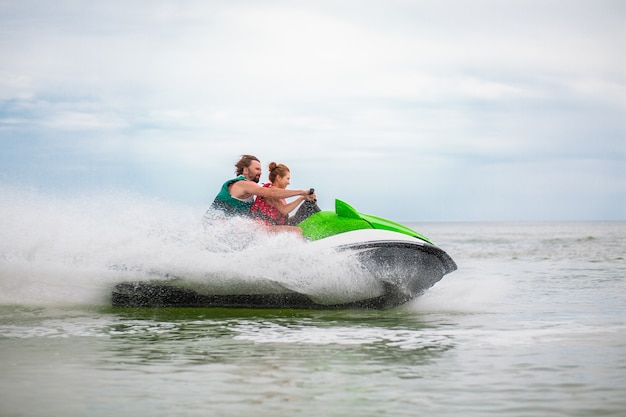Couple having fun on water scooter summer sea activity