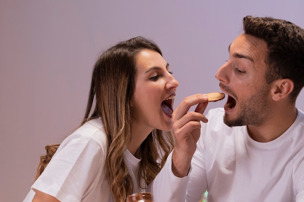 Couple having fun with biscuits