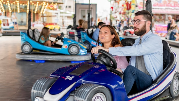 Couple having fun with bumper cars at the amusement park