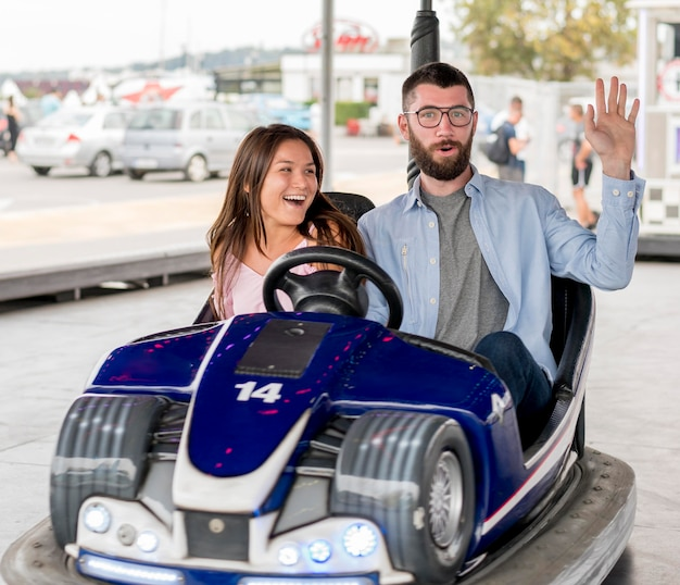 Couple having fun with bumper cars
