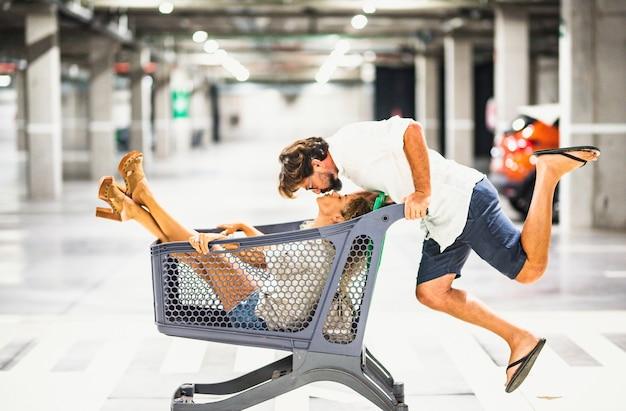 駐車場でショッピングカートを楽しんでいるカップル、夫はショッピングトロリーの中に座っている彼ののんきな妻にキスします。カップルはスーパーマーケットのカートを楽しんでいます