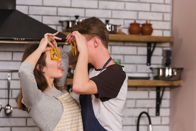 Couple having fun with slices of pepper in kitchen