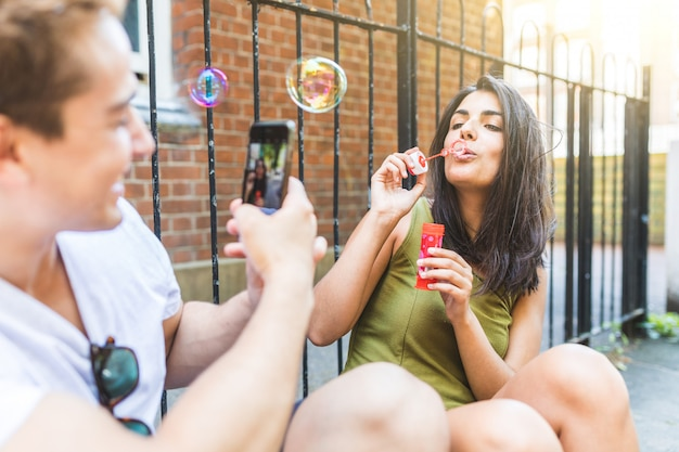 Couple having fun with soap bubbles in london