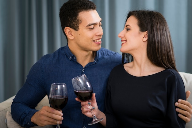Couple having a glass of wine while sitting on the couch