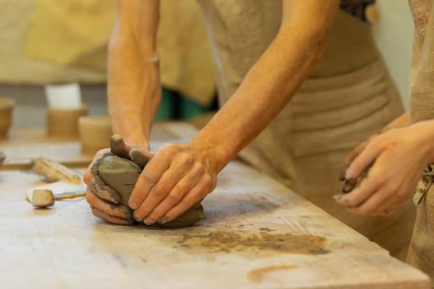 マスタークラスを持つカップル。学生が近くに滞在している間、強い男が木製のテーブルに新鮮な粘土の断片をしっかりと押し付けます