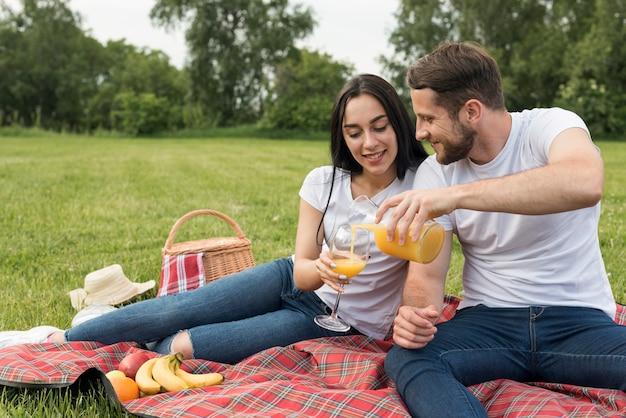 Couple having orange juice on picnic blanket