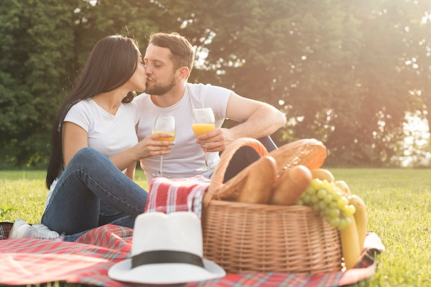 Couple having orange juice on picnic blanket