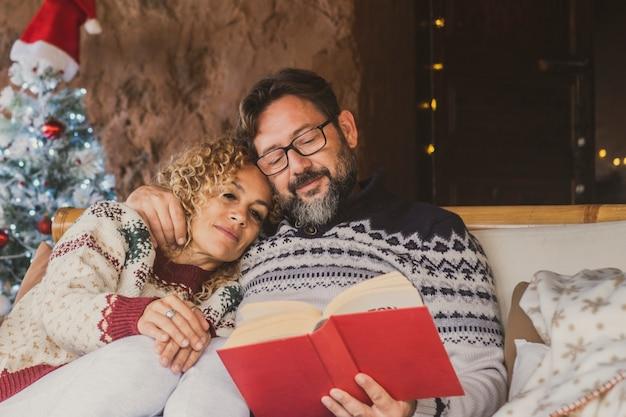 クリスマスツリーと一緒にソファでくつろいでいるカップル