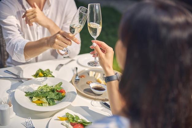 낭만적 인 데이트를하고 레스토랑에서 테이블에 앉아 안경을 부딪 치는 부부