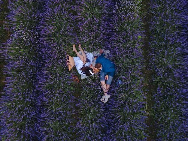 Пара, устраивающая романтический пикник на свидании на лавандовом поле, вид сверху