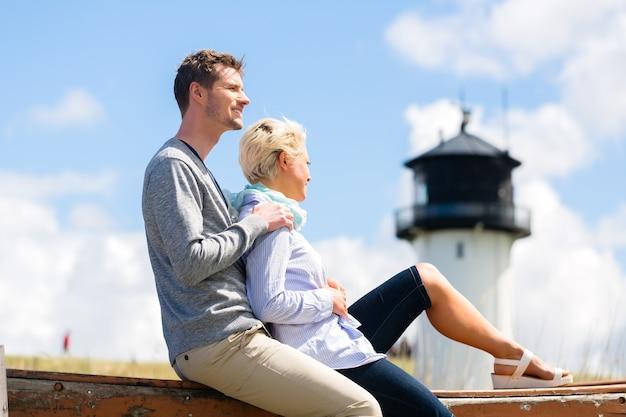 등대 앞의 독일 북해 해변 모래 언덕에서 낭만적 인 휴가를 보내는 커플