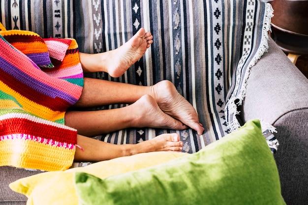自宅のソファに裸の足と色付きのカバーでセックス活動の概念を持っているカップル