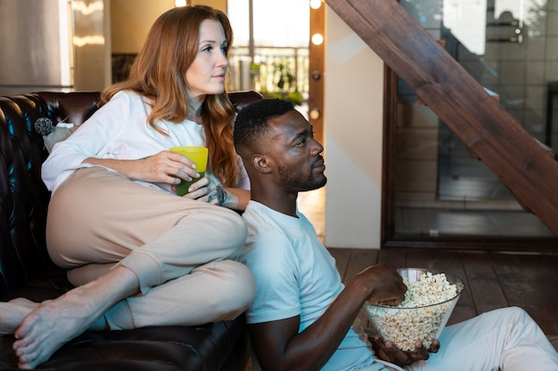 映画を見ながらポップコーンを持っているカップル