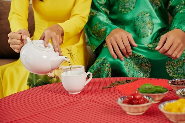 テトのお祝いでお茶を持っているカップル