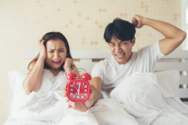 Couple having trouble with getting up early in the morning on the bed