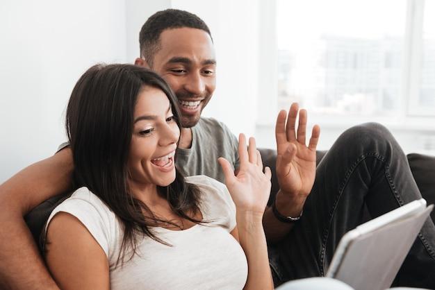 Пара, имеющая видео-чат на планшетном компьютере дома и размахивая. глядя на планшетный компьютер.
