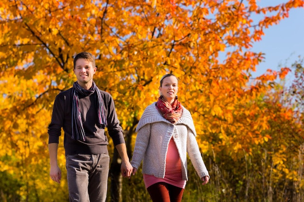 Couple having walk in front of colorful trees in autumn